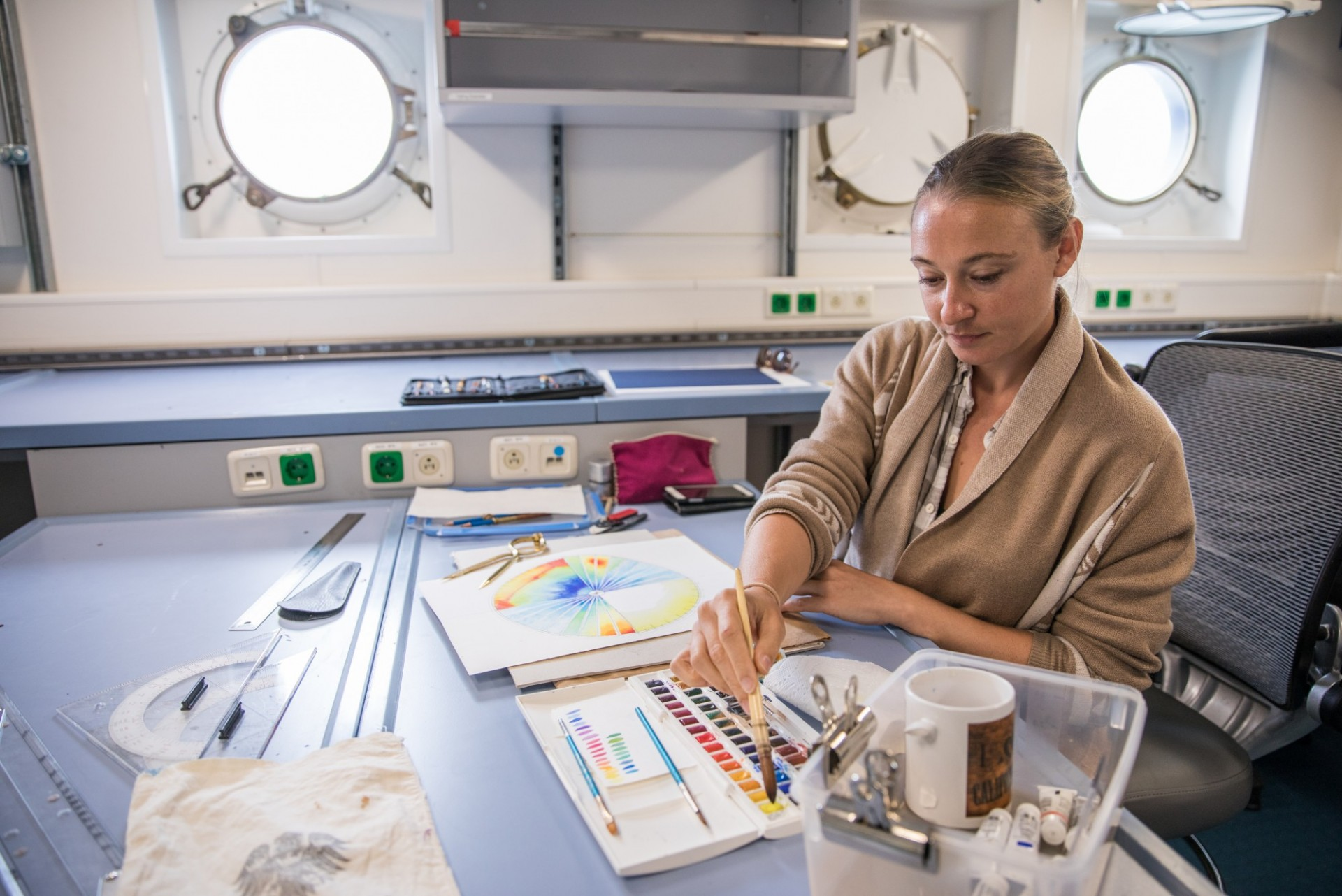 Lauren working in the R/V Falkor's dry lab, creating watercolour interpretations of the multibeam sonar acquisition display screens that show the seafloor mapping in real time.